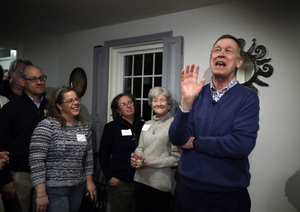 Former Colorado Gov. John Hickenlooper speaks at a campaign house party in Manchester, N.H.