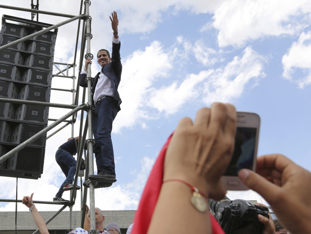 Venezuelan Congress President Juan Guaido, an opposition leader who declared himself interim president, waves from the scaffolding after speaking at a rally demanding the resignation of Venezuelan President Nicolas Maduro in Caracas, Venezuela, on Monday. The United States and about 50 other countries recognize Guaido as the rightful president of Venezuela, while Maduro says he is the target of a U.S.-backed coup plot.