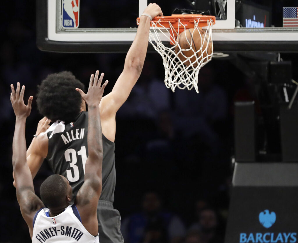 Brooklyn's Jarrett Allen dunks while being defended by Dallas' Dorian Finney-Smith during the Nets' 127-88 win Monday at New York.