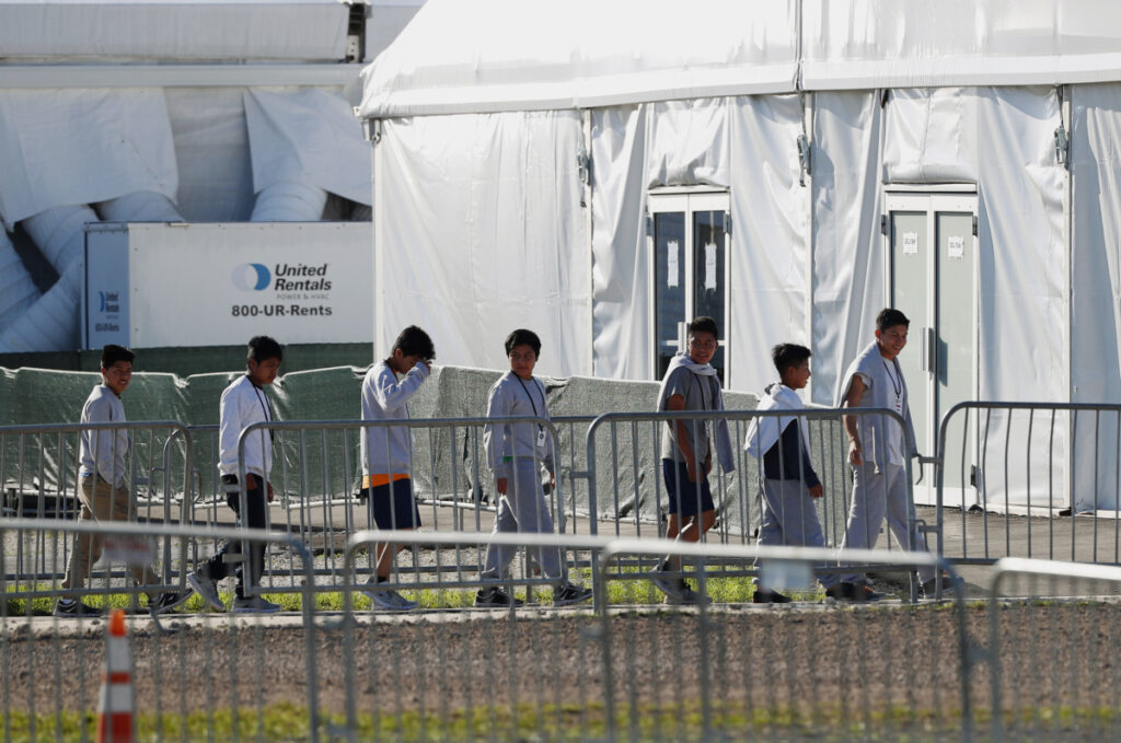 """Immigrant children line up outside a tent at a shelter in Florida last month. Migrants continue to push toward the Mexican border in record numbers. """"The system is well beyond capacity,"""" a border security official said Tuesday."""