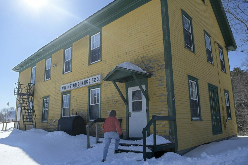 Kennebec Journal photo by Andy Molloy   Cheryl Joslyn enters the Arlington Grange, which holds Whitefield's library, on Tuesday. The library is hoping to acquire the structure.