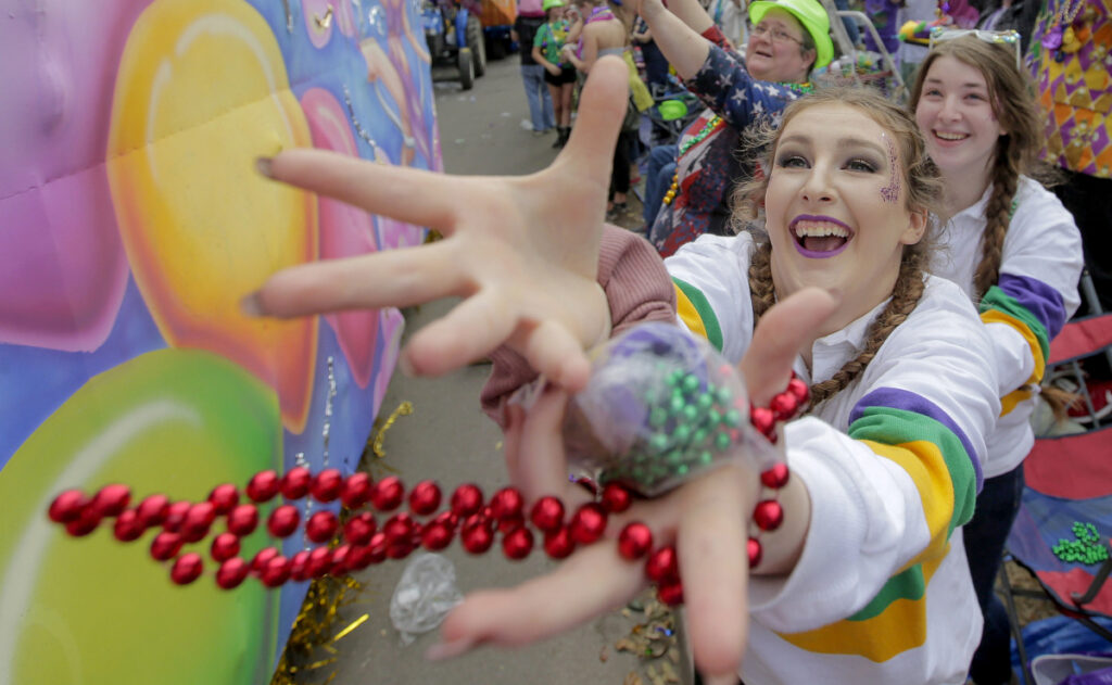 A Mardi Gras celebrant catches a bauble tossed from a float along the Uptown route in New Orleans on Sunday.