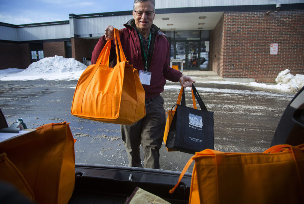 Leonard Guralnick, a Meals on Wheels volunteer, loads bags of food into his car before delivering them to clients of the program in Portland. There's a chronic waiting list of 400 to 1,500 people who qualify for the program but can't get it because funding doesn't go far enough. Two measures now advancing in the Legislature seek to improve the program.
