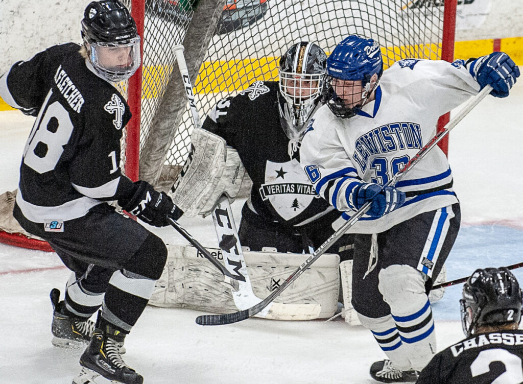 St. Dominic Academy goalie Miloslav Gaston Fuksa eyes the puck as it is tipped by Lewiston's Tyler Marcoux during Tuesday night's playoff game at the Androscoggin Bank Colisee in Lewiston.