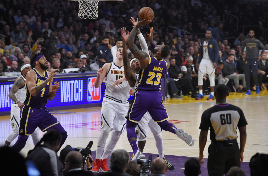 Los Angeles Lakers forward LeBron James (23) shoots and scores as Denver Nuggets forward Torrey Craig, second from right, defends and center Nikola Jokic, center, watches along with Lakers center JaVale McGee, left, during the first half of an NBA basketball game Wednesday, March 6, 2019, in Los Angeles. With that basket, James moved past Michael Jordan for fourth place on the NBA career scoring list. (AP Photo/Mark J. Terrill)