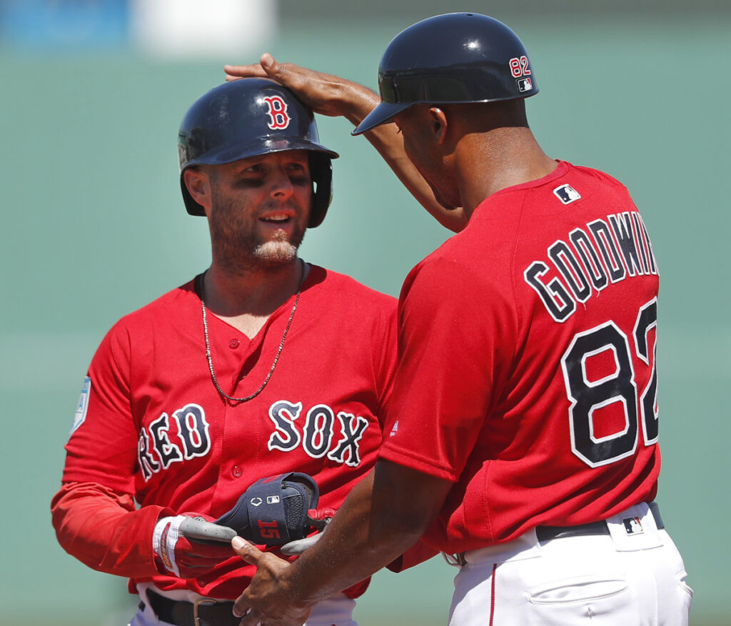 Dustin Pedroia is congratulated by Red Sox first-base coach Tom Goodwin after hitting a single in the first inning Thursday against the Minnesota Twins.