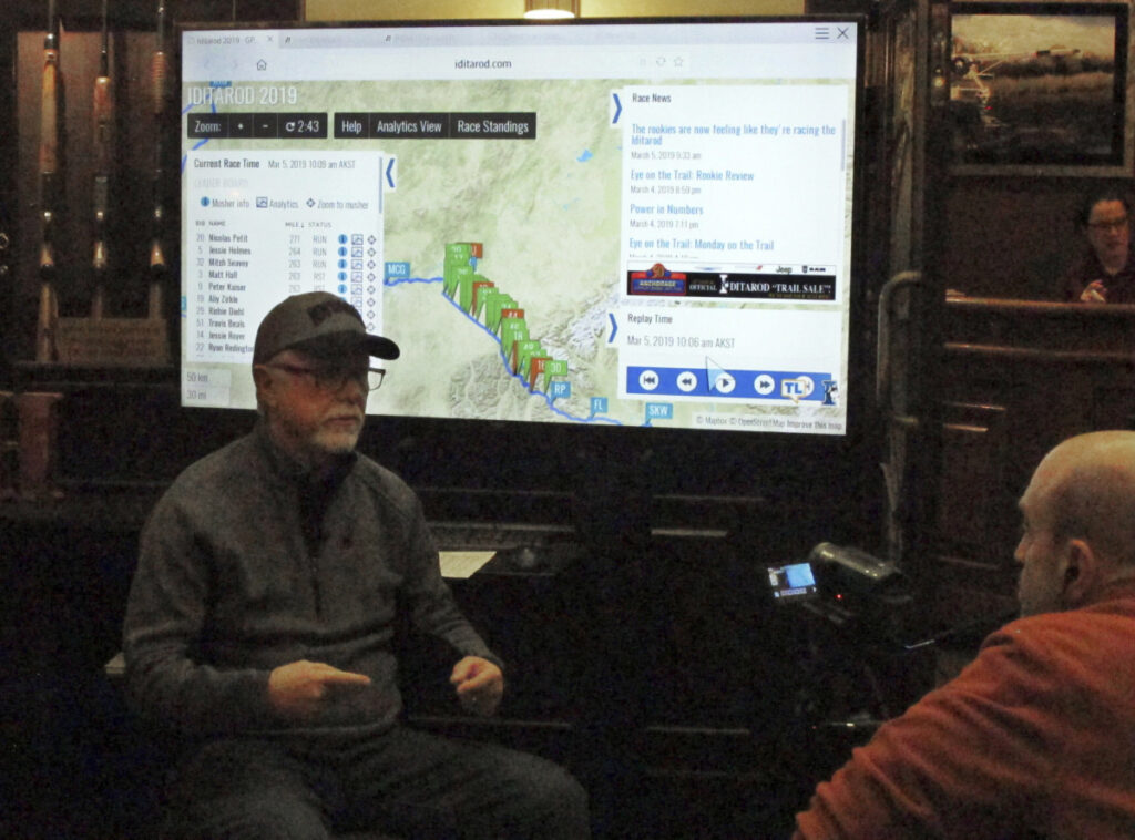Iditarod spokesman Chas St. George sits in front of a large screen set up inside a hotel in Anchorage on Tuesday for public updates in the 1,000-mile Iditarod Trail Sled Dog Race.