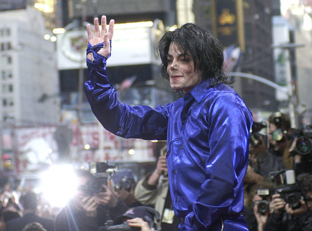 "Michael Jackson waves to crowds gathered to see him at his first-ever in-store appearance in New York on Nov. 7, 2001. The producers of ""The Simpsons"" are removing a classic episode that featured the voice of Jackson."