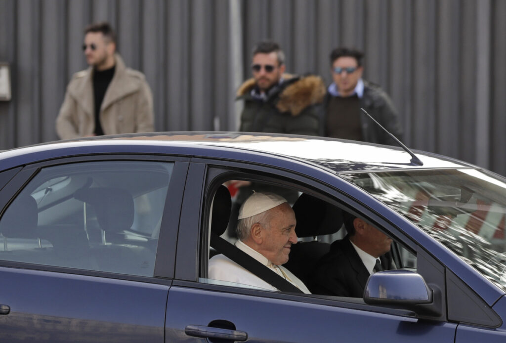 Pope Francis waves as he leaves St. John Lateran Basilica after meeting clergy members in Rome on Thursday.