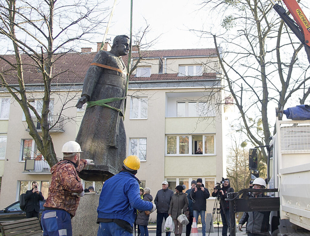 Workers dismantle a statue of the late Solidarity-era priest Henryk Jankowski in Gdansk, Poland, on Friday. City councilors decided to remove it amid allegations Jankowski sexually abused minors.