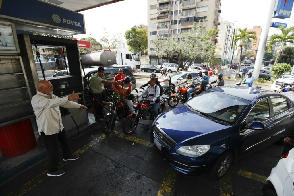 Customers line up at a gas station Friday in Caracas, Venezuela. Much of Venezuela was still without electricity Friday amid the country's worst-ever power outage, raising tensions in a nation already on edge from ongoing political turmoil.