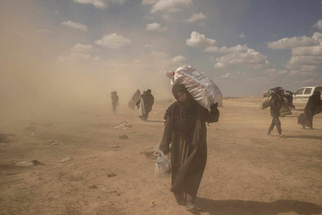 A woman carries supplies from a reception area for people evacuated from the last shred of territory held by Islamic State militants, outside Baghouz, Syria, on Wednesday.