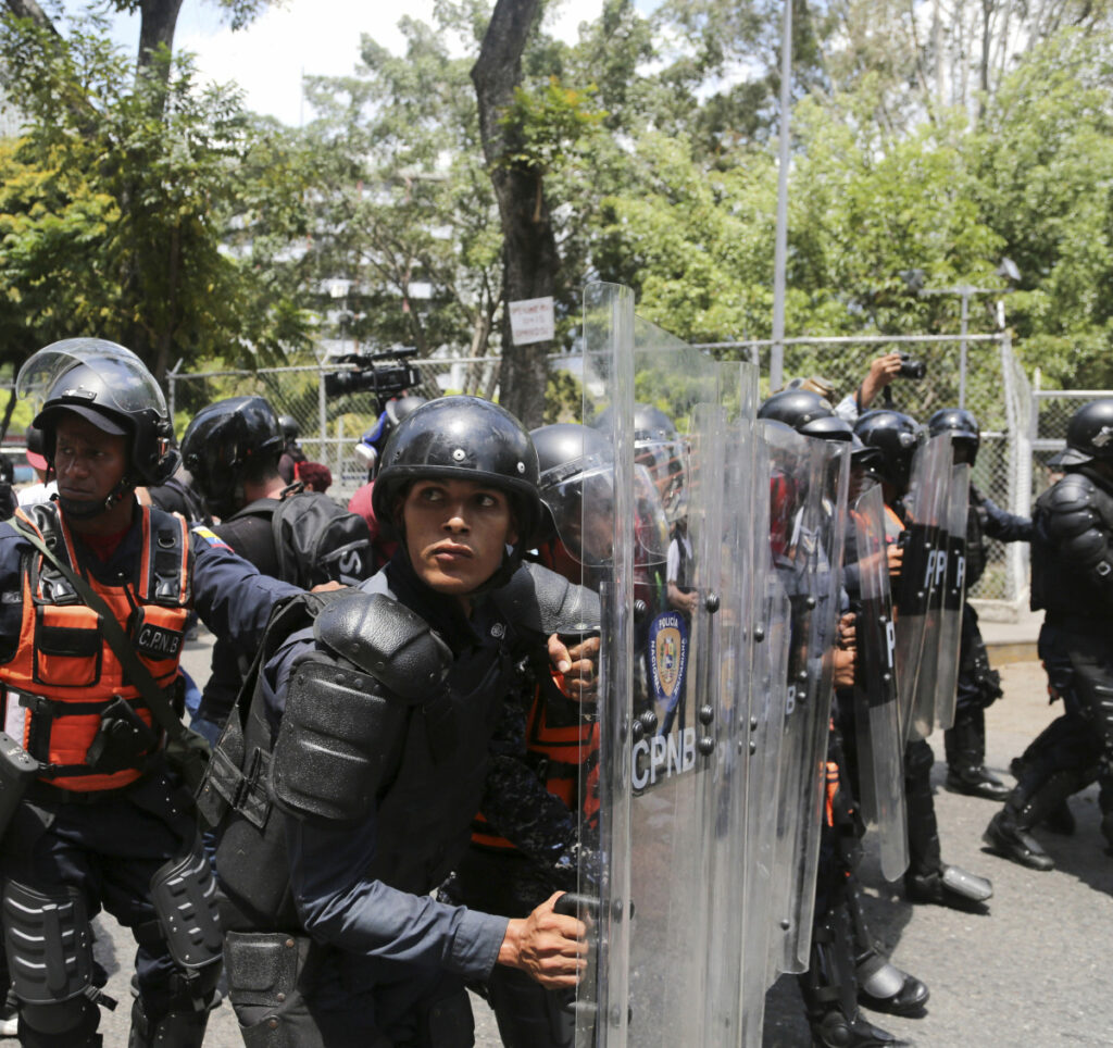 A cordon of Venezuelan National Police officers retreats when confronted by demonstrators who were temporarily blocked by police from getting to a rally against the government of President Nicolas Maduro in Caracas on Saturday.