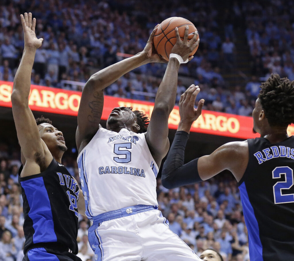 Nassir Little of North Carolina drives to the basket Saturday night between Javin DeLaurier, left, and Cam Reddish of Duke during the first half of their Atlantic Coast Conference men's basketball game. North Carolina won, 79-70.