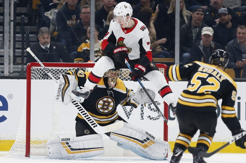 Ottawa's Brady Tkachuk jumps in front of Bruins goalie Tuukka Rask to avoid a shot by teammate Thomas Chabot during Boston's 3-2 win Saturday night at TD Garden.