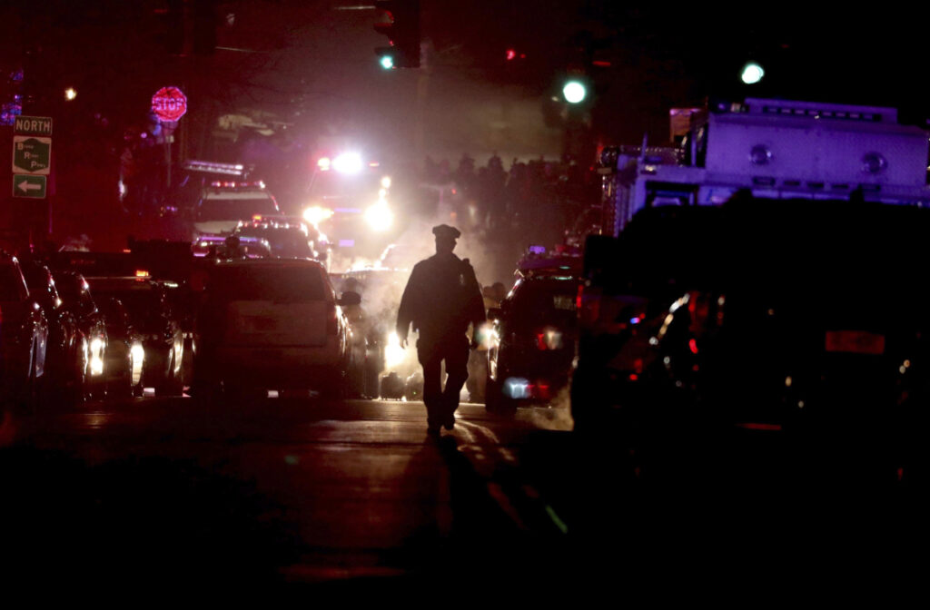 An officer walks the street as authorities from various local departments surround Lawrence Hospital in Bronxville, N.Y., late Sunday night as police searched inside the hospital for a possible gunman. All local roads around the hospital were closed as heavily armed police swarmed the area.