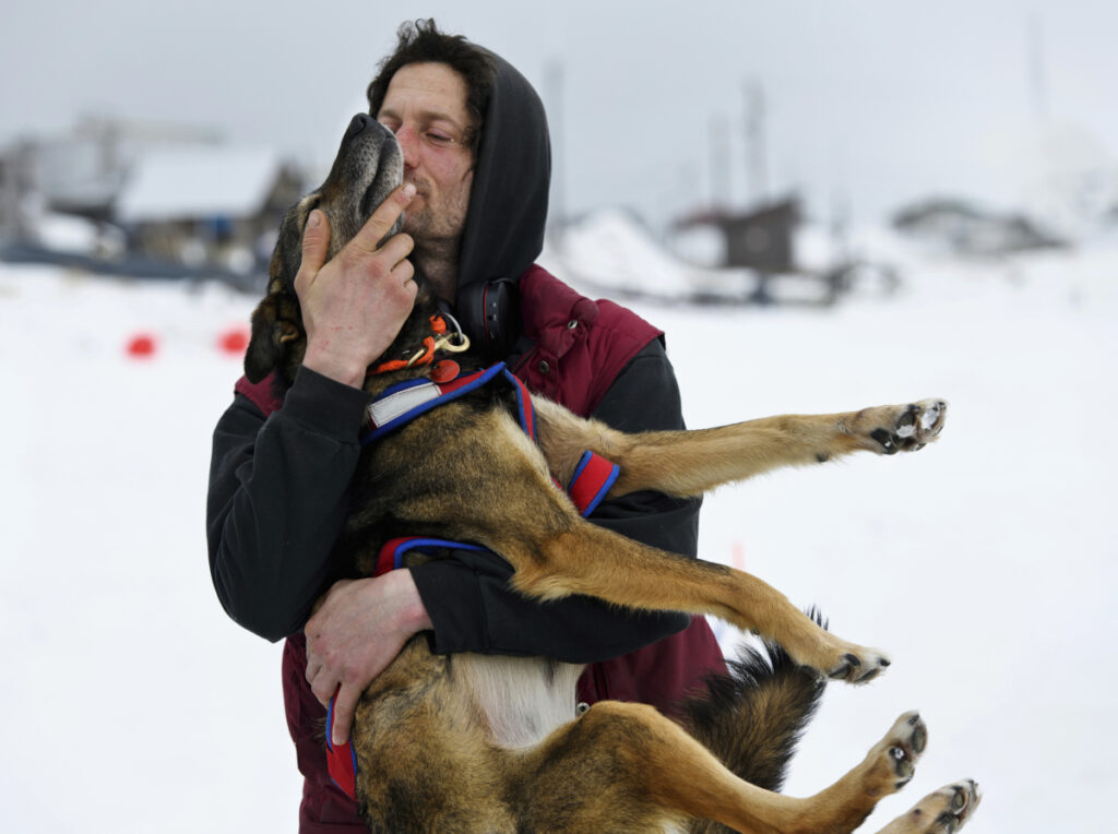 Nicolas Petit hugs one of his dogs before they leave Unalakleet, Alaska, during the Iditarod Trail Sled Dog Race on Sunday.
