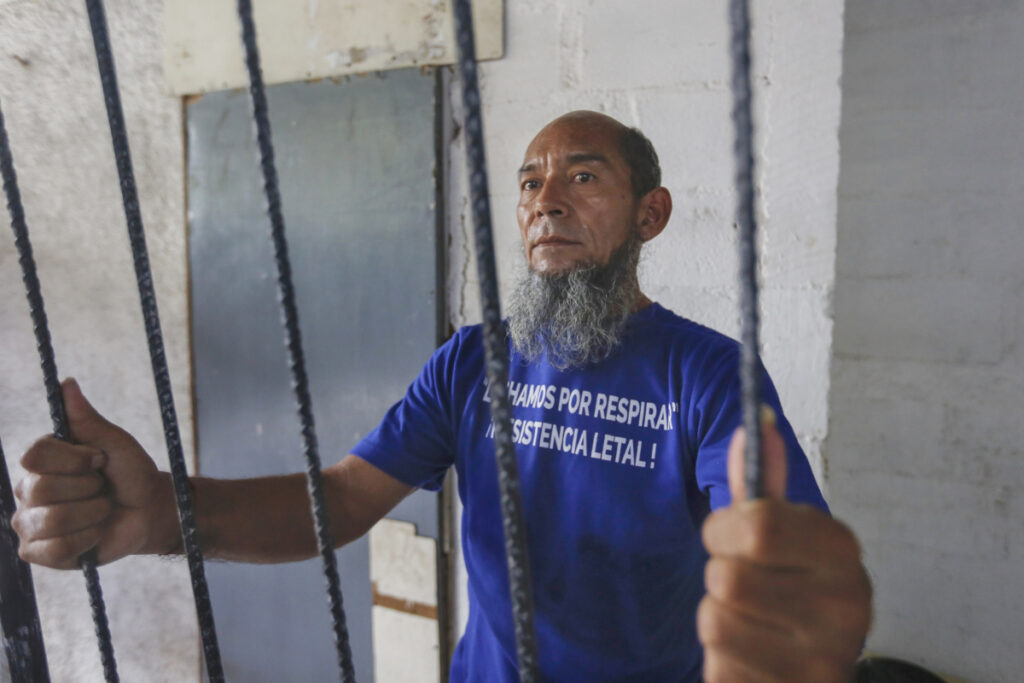 Last week, Alex Vanegas holds on to the iron bars he had installed on the porch of his apartment in Managua, Nicaragua, to symbolize his house arrest.