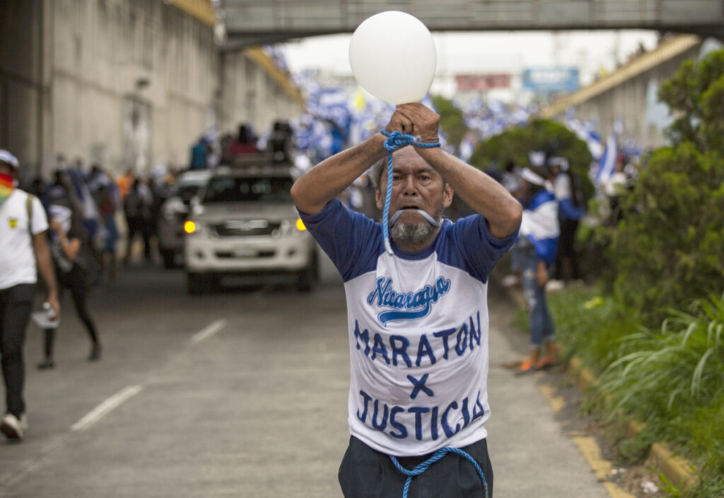 Alex Vanegas runs with his hands tied and his mouth gagged during a protest march against the government of President Daniel Ortega in Managua, Nicaragua, last July. During the unrest that rocked Nicaragua last year, Vanegas became a prominent symbol of opposition to Ortega, instantly recognizable for his salt-and-pepper beard and shirts emblazoned with anti-government slogans as he jogged through the streets of Managua in the blue and white of his country's flag.