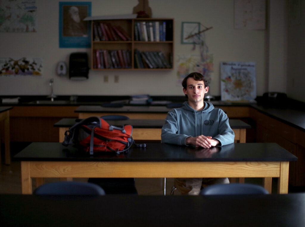 Matt Hogenauer poses for a portrait in a biology classroom at Falmouth High School. Hogenauer takes arthritis medication that suppresses his immune system and makes him vulnerable to infectious diseases. He strongly supports a bill that would eliminate all non-medical exemptions for school-required vaccines.
