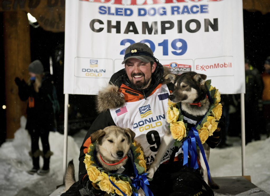 Peter Kaiser poses with his lead dogs, Morrow, left, and Lucy, on Wednesday in Nome, Alaska, after winning the Iditarod Trail Sled Dog Race. It's the first Iditarod victory for Kaiser in his 10th attempt.