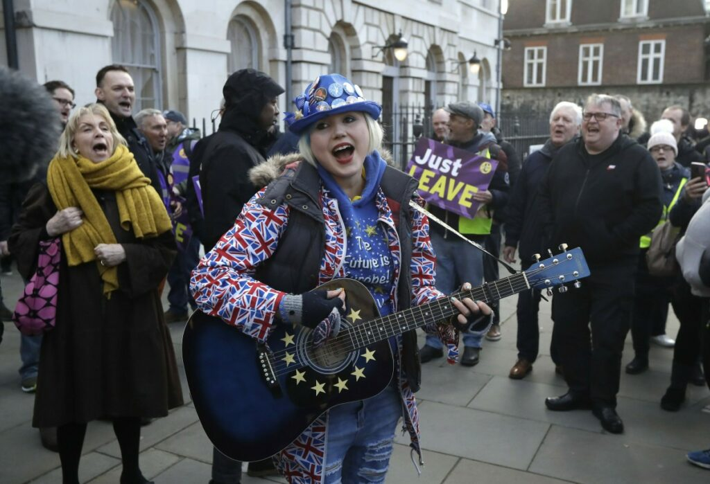 An anti-Brexit supporter of remaining in the European Union, center, plays a guitar as she's surrounded by pro-Brexit supporters outside the Houses of Parliament in London on Thursday.