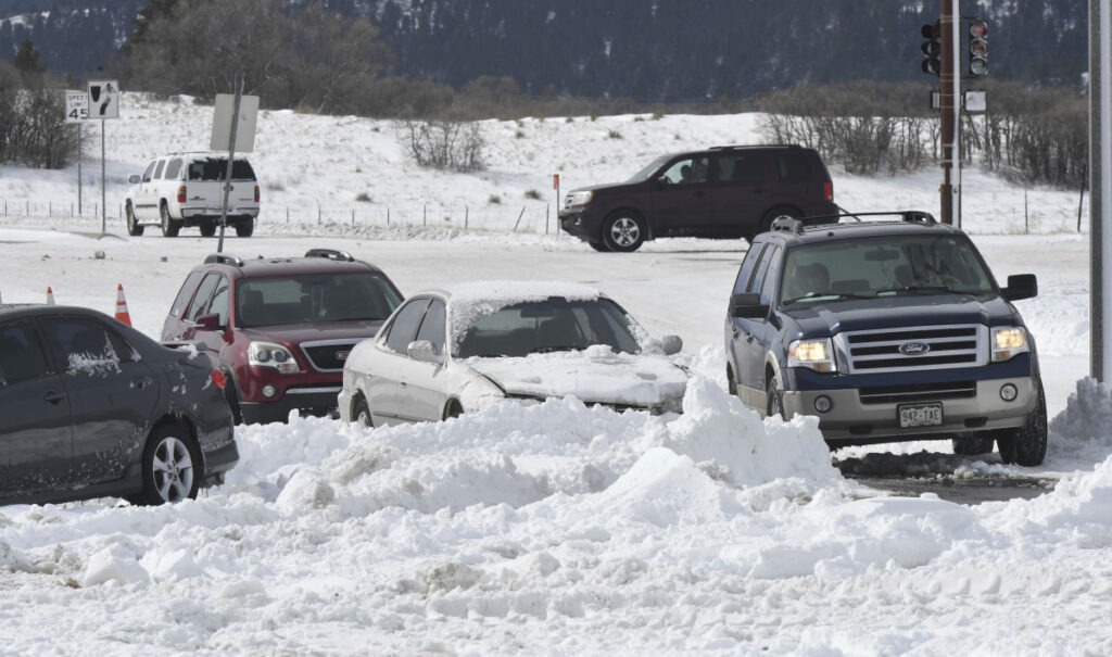 A driver makes his way through an obstacle course of abandoned vehicles Wednesday in Monument, Colo., on Thursday.