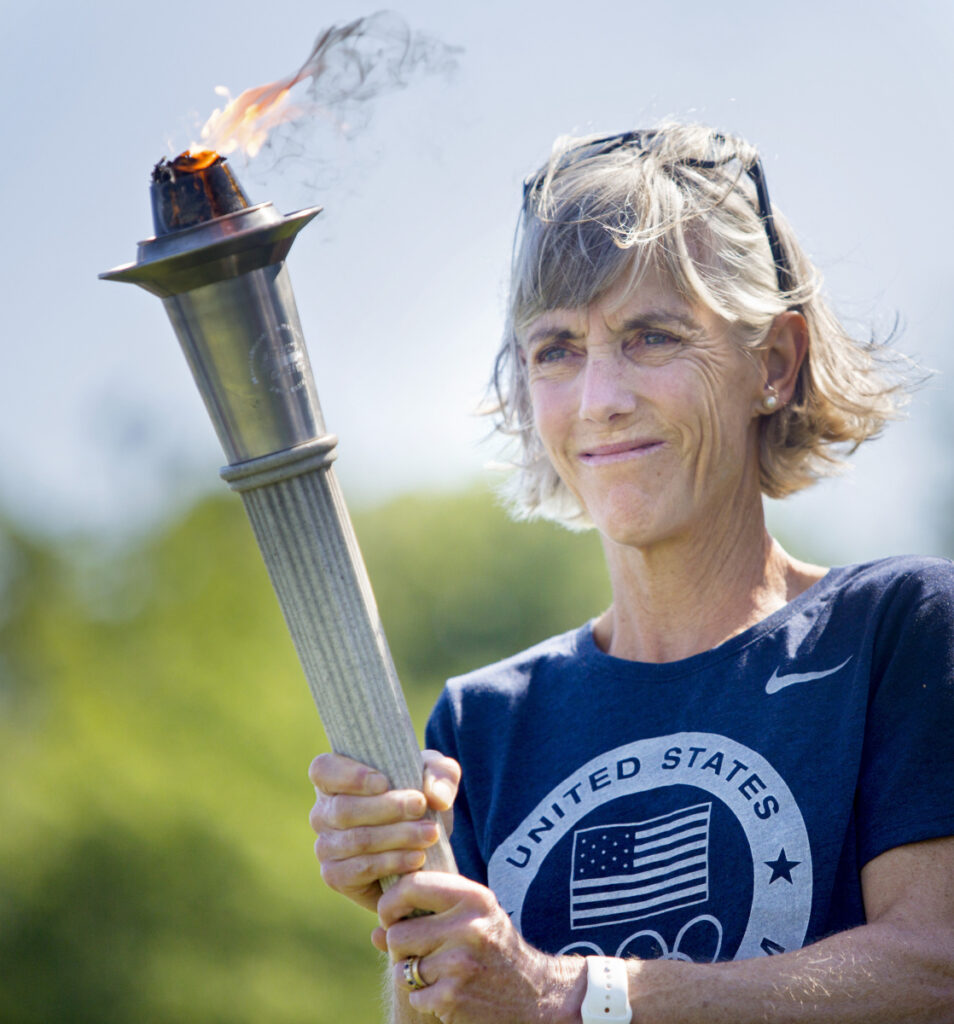 Joan Benoit Samuelson carries a torch during opening ceremonies for the TD Beach to Beacon High School Mile in August 2016. (Photo by Derek Davis/Staff Photographer)
