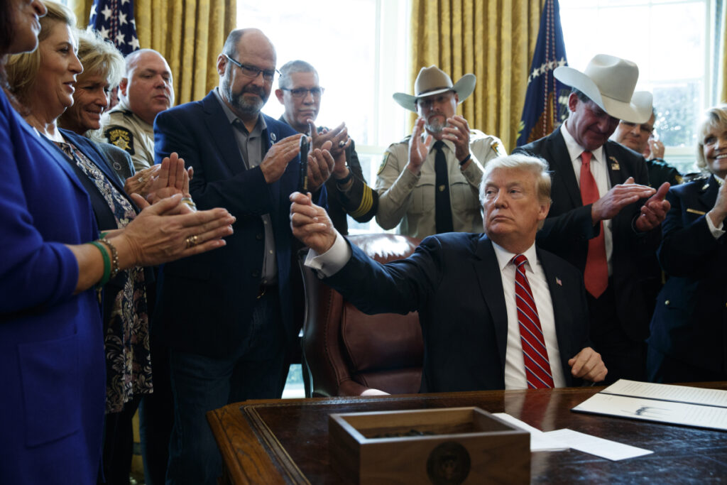 President Trump hands out a pen after signing the first veto of his presidency Friday in the Oval Office of the White House. His veto overruled a congressional resolution opposing his declaration of a national emergency at the U.S.-Mexico border