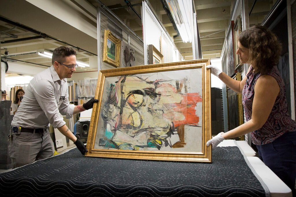 """In August 2017, """"Woman-Ochre,"""" a painting by Willem de Kooning, is readied for examination by University of Arizona Museum of Art staff members Nathan Saxton and Kristen Schmidt in Tucson."""