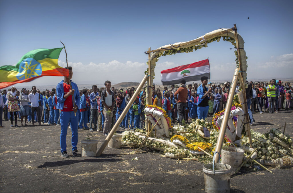 Students stand next to floral tributes Friday at the scene where the Ethiopian Airlines Boeing 737 Max 8 crashed shortly after takeoff Sunday, killing all 157 on board. The students walked an hour and a half from their school to pay their respects.