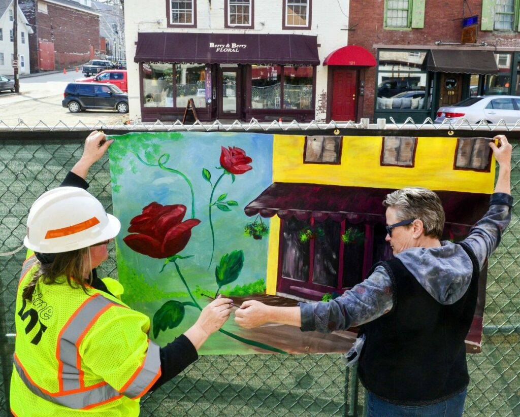Kennebec Journal file photo by Joe Phelan   Karen Libby, the Maine Department of Transportation resident for the Water Street project, left, and Deb Fahy, executive director of the Harlow Gallery, hang a mural in April 2018 on the sidewalk side of the construction fence on on Water Street in downtown Hallowell.