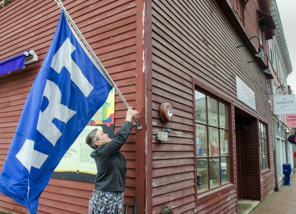 Kennebec Journal photo by Joe Phelan Executive director Deb Fahy puts out a large flag that says ART just before opening up at noon Friday at the Harlow Gallery on Water Street in Hallowell. Fahy is stepping down after 14 years as director.