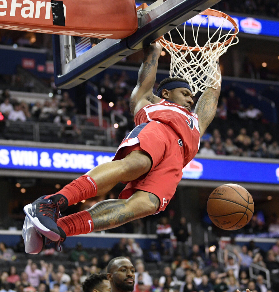 Bradley Beal of the Washington Wizards hangs on the rim after a dunk Friday night. Beal scored 40 points but it wasn't enough to prevent the Charlotte Hornets from coming away with a 116-110 victory.