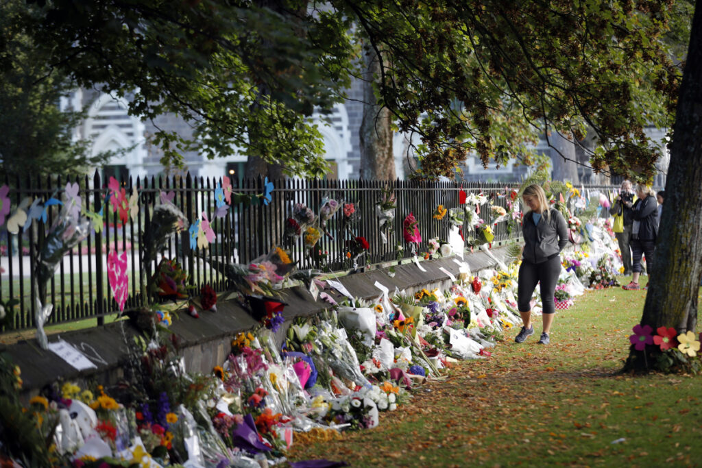 Mourners pay their respects at a makeshift memorial at the Botanical Gardens in Christchurch, New Zealand, Saturday. Brenton Tarrant is suspected of killing 49 people at two mosques.