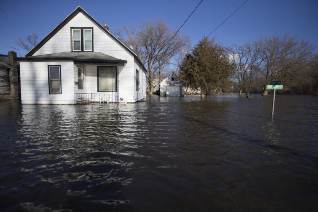 Floodwaters lap close to the front yards of homes on South Sherman Avenue in Freeport, Ill., on Friday. Rising waters along the Pecatonica and Rock rivers have flooded homes in northern Illinois.