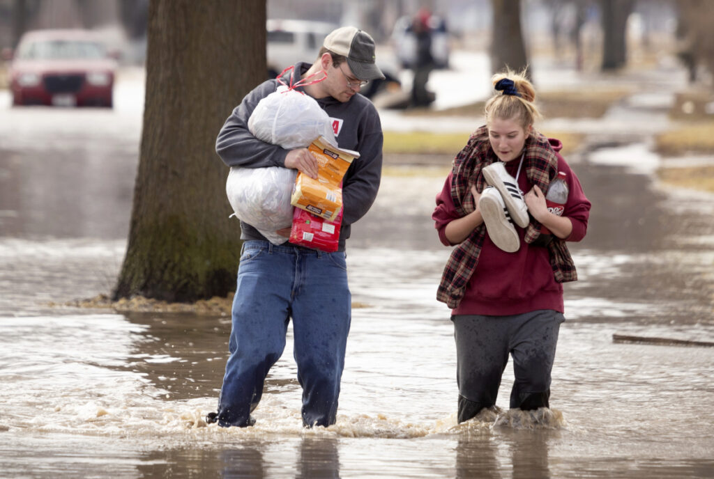 Anthony Thomson, left, and Melody Walton make their way out of a flooded neighborhood Sunday in Fremont, Neb.