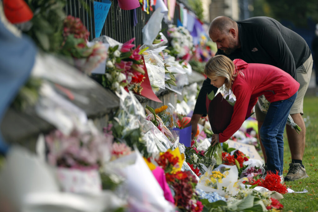 Mourners lay flowers on a wall at the Botanical Gardens in Christchurch, New Zealand, on Saturday.