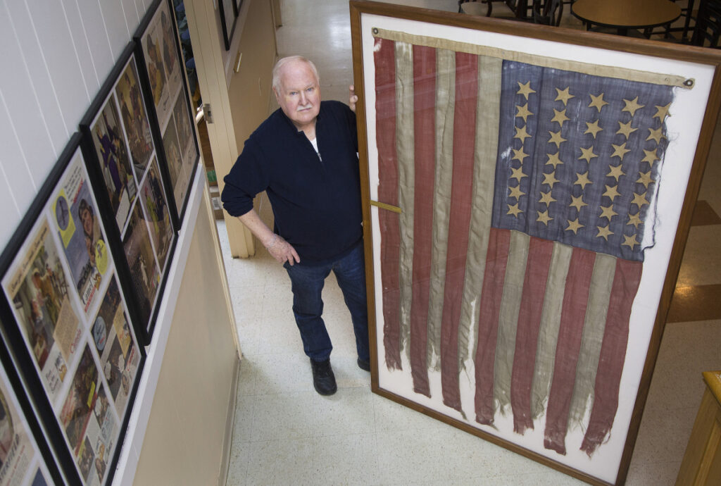 Lee Humiston of the Maine Military Museum receives flag from the Civil War that he says was the first to fly over Texas shores. The flag belonged to Major James H. Whitmore of the Fifteenth Maine Regiment.