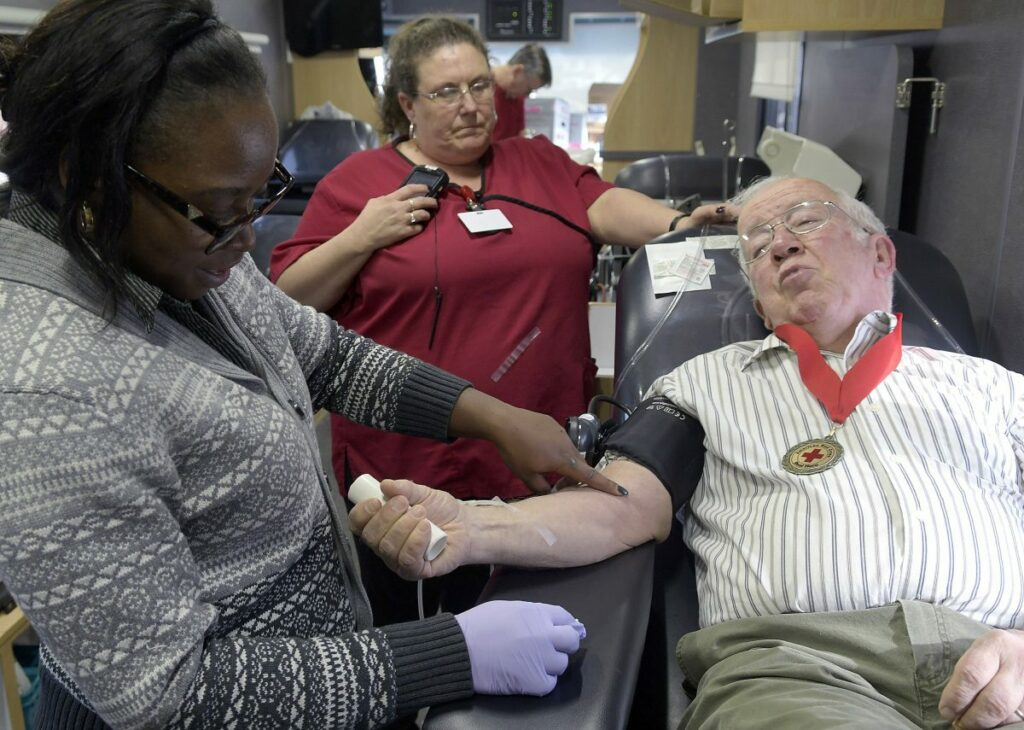 Red Cross phlebotomists Meika Reed, left, Laura Landry draw blood on Wednesday from Jack Schrader in a Red Cross van at the Augusta branch of Kennebec Savings Bank.