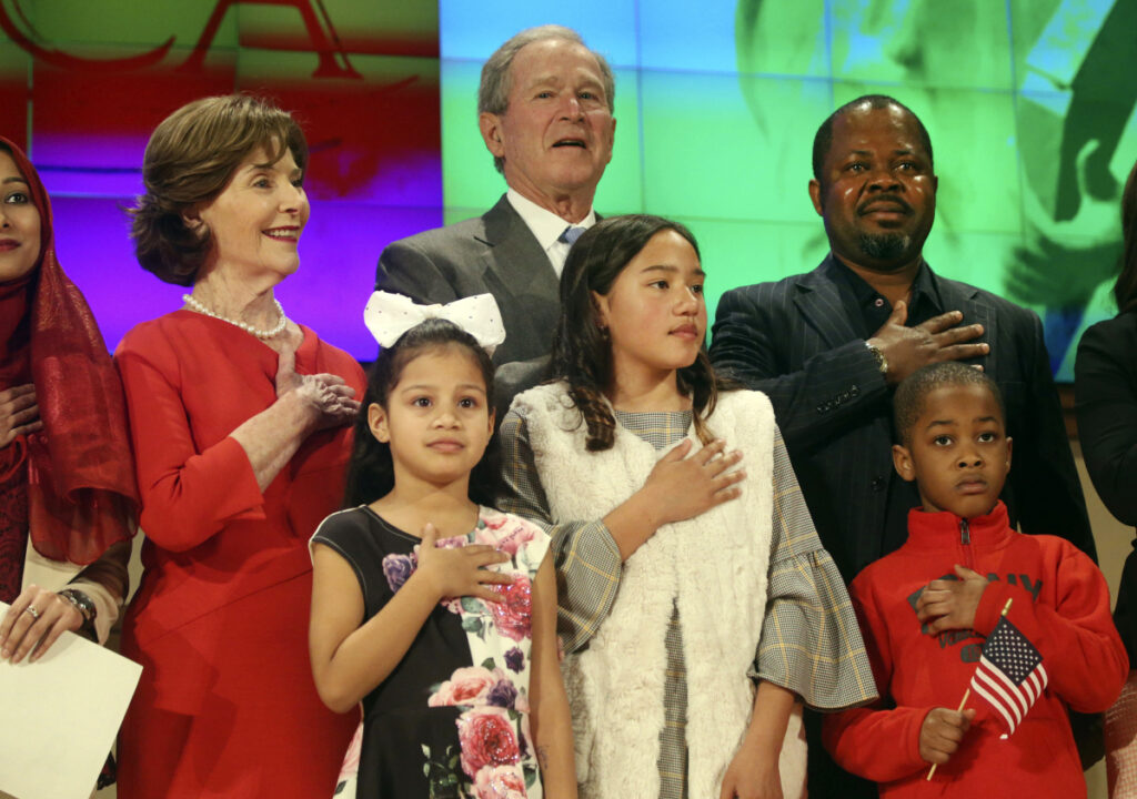 Former President George W. Bush and former first lady Laura Bush recite the pledge of allegiance Monday with new U.S. citizens, including Felix Odeh, top right, of Nigeria, during a naturalization ceremony at the George W. Bush Presidential Center in Dallas. Forty-nine people became American citizens at the ceremony.