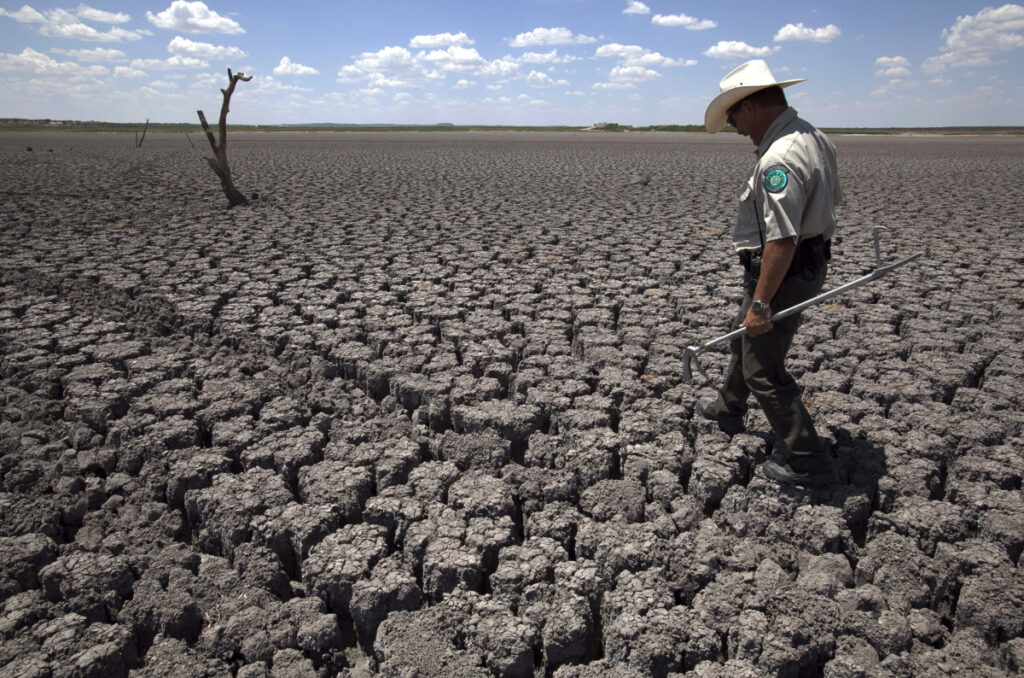 A Texas State Park police officer walks across the parched lake bed of O.C. Fisher Lake, in San Angelo, Texas, in 2011. The impacts of record-breaking heat and years of low rainfall can be felt years after a dry spell passes.