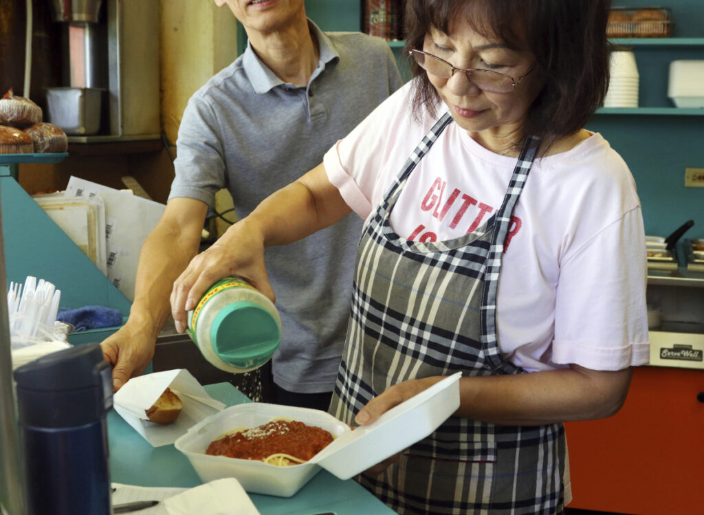 Belinda Lau, manager of the Wiki Wiki Drive Inn takeout restaurant in Honolulu, prepares an order of spaghetti in a styrofoam container. The company fears that a ban on plastic containers would cut too deeply into profits.