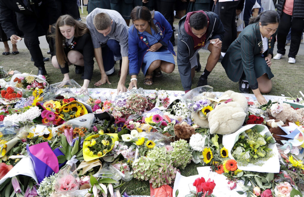 Students from Christchurch high schools light candles at a tribute at the Botanical Gardens in Christchurch, New Zealand, on Tuesday as relatives and friends of the 50 victims from Friday's shootings began to bury the dead.