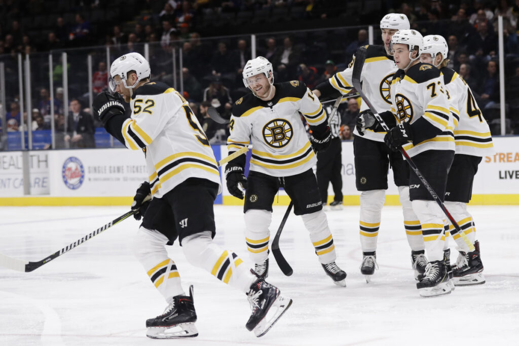 Boston's Sean Kuraly skates back to his bench with teammates after scoring a goal in the first period Tuesday night at Uniondale, N.Y.