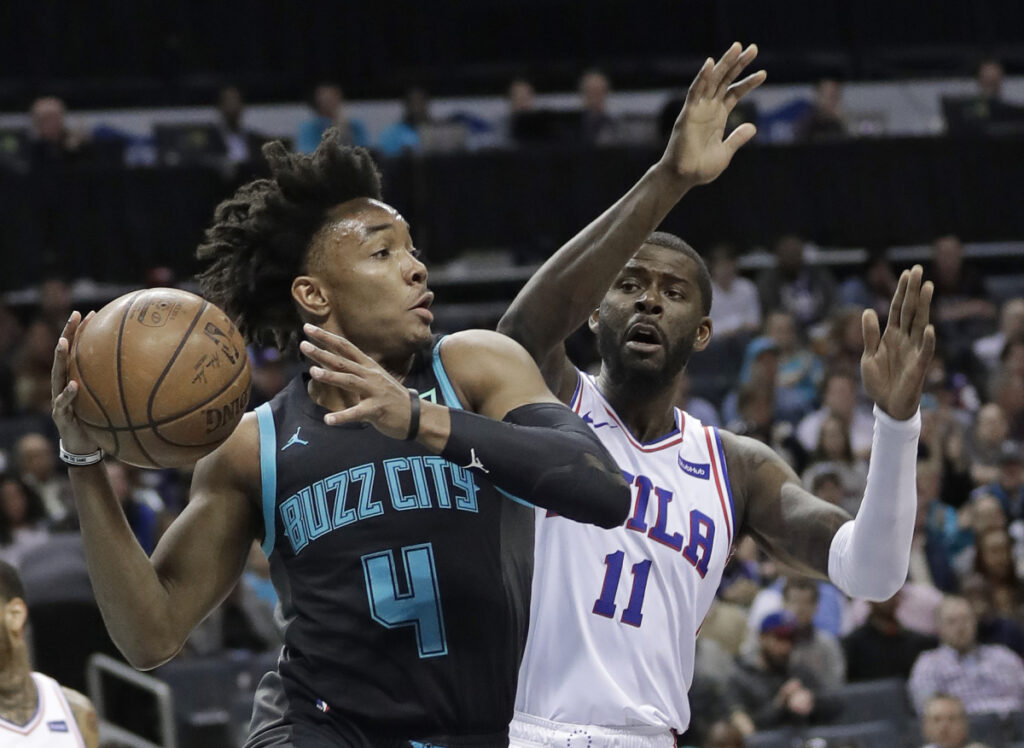 Charlotte's Devonte' Graham looks to pass as Philadelphia's James Ennis III defends during Tuesday's game at Charlotte, N.C.