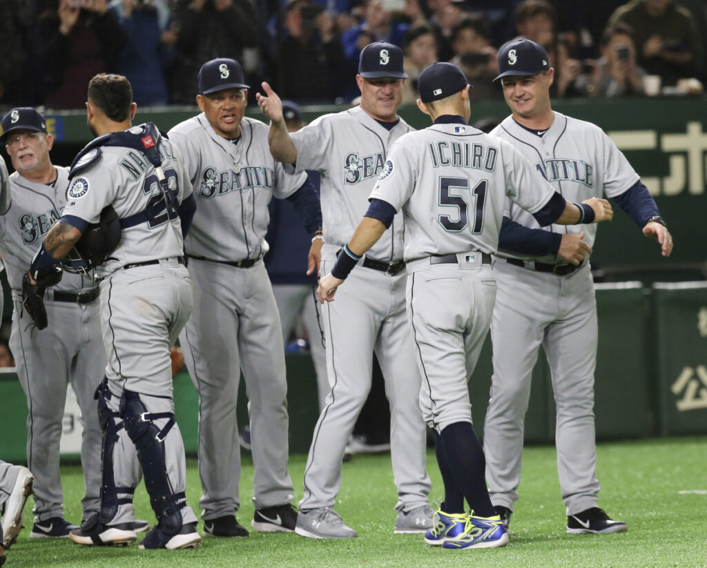 Seattle right fielder Ichiro Suzuki celebrates with teammates after defeating the Oakland Athletics 9-7 at Tokyo Dome on Wednesday morning.