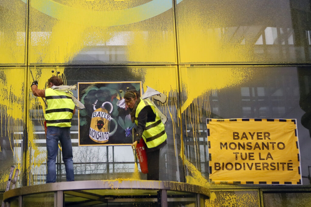 """French activists of Attac spray-paint the Paris headquarters of Bayer AG last week to protest its production of pesticides. Bayer is battling dozens of lawsuits over the weed killer Roundup, made by its American subsidiary Monsanto. """"Bayer Monsanto Kills Biodiversity,"""" the placard reads."""