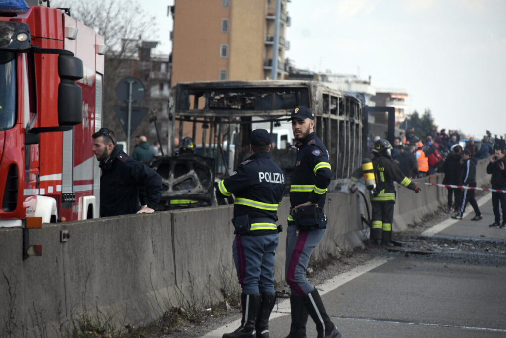 Firefighters and police officers stand guard over a school bus in San Donato Milanese, Italy, on Wednesday after the driver kidnapped 51 children and their chaperones and threatened to kill them.