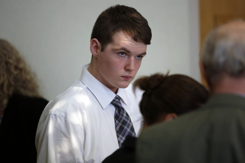 Dominic Sylvester, now 18, confers with lawyers during a recess in his hearing Thursday in West Bath District Court. A judge will decide whether the Bowdoinham teenager will be tried as an adult in the death of his grandmother.